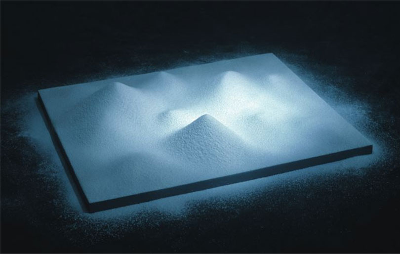 Oslo, Crushed aspirin, wood and blue light, 1998. In this work, aspirin is ground into a fine powder and poured slowly over a platform to create a landscape reminiscent of mountains, hills, and valleys. For a 2012 solo exhibition at the Kunsthalle in Düsseldorf, Koo presented an expanded version using powder made by grinding down dust and rocks assembled over several years.