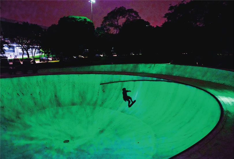 """ARROGATION, Mixed Media, 32nd São Paulo Biennial, 2016. A large outdoor sculpture in the form of a skating park. The sculpture is made of light-responsive materials, appearing light gray during the day and shining fluorescent green at night. It was exhibited at the 32nd São Paulo Biennale, which had the theme of """"live uncertainty."""""""