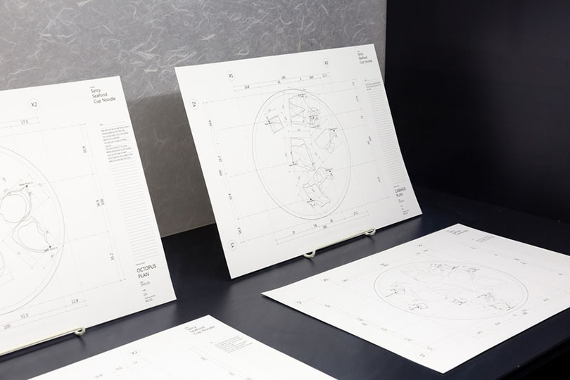 """Detailed installation view of MINJA GU's The Authentic Quality – Spicy Seafood Noodle, 2019, CAD drawings printed on A3 paper, 11 pieces, at """"Take ( ) at Face Value,"""" Korean Cultural Centre Australia, Sydney, 2019. Photo by Documentary Photography. Courtesy the artist and Korean Cultural Centre Australia."""