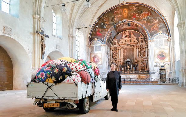 "Artist Kimsooja stands with a truck used for her 2007 performance video ""Bottari-Truck Migrateurs"" inside Saint-Louis Chapel in Poitiers, France. The work is part of the initial edition of the French city's new art festival ""Traversees / Kimsooja."" MOON SO-YOUNG"