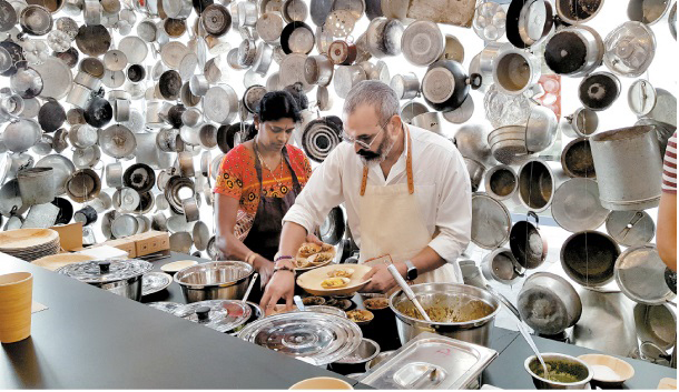 Indian artist Subodh Gupta cooks cuisine from his home country inside an installation he created using Indian pots and pans at Maison de L'Architecture in Poitiers, France. MOON SO-YOUNG