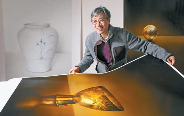 """The renowned photographer Koo Bohnchang shows a photo from his new """"Gold"""" series at his studio. Photo© PARK SANG-MOON"""