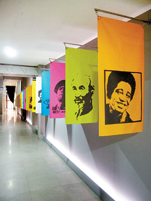 Outside the exhibit hall are colorful flags with the faces of different figures in modern history, such as Che Guevara.
